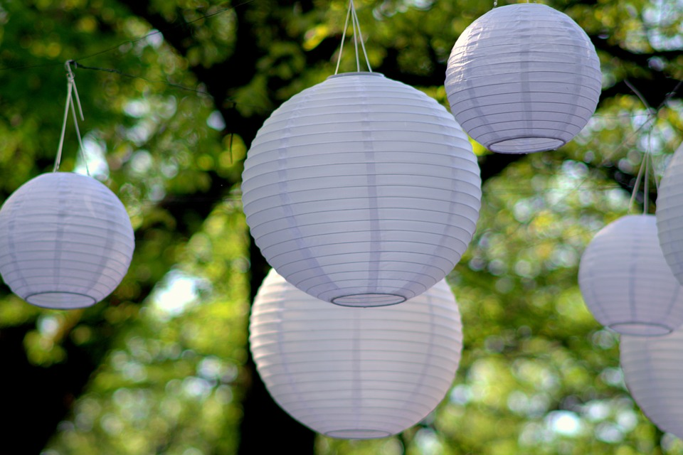 Double duty decor ideas- hang white paper lanterns from a tree